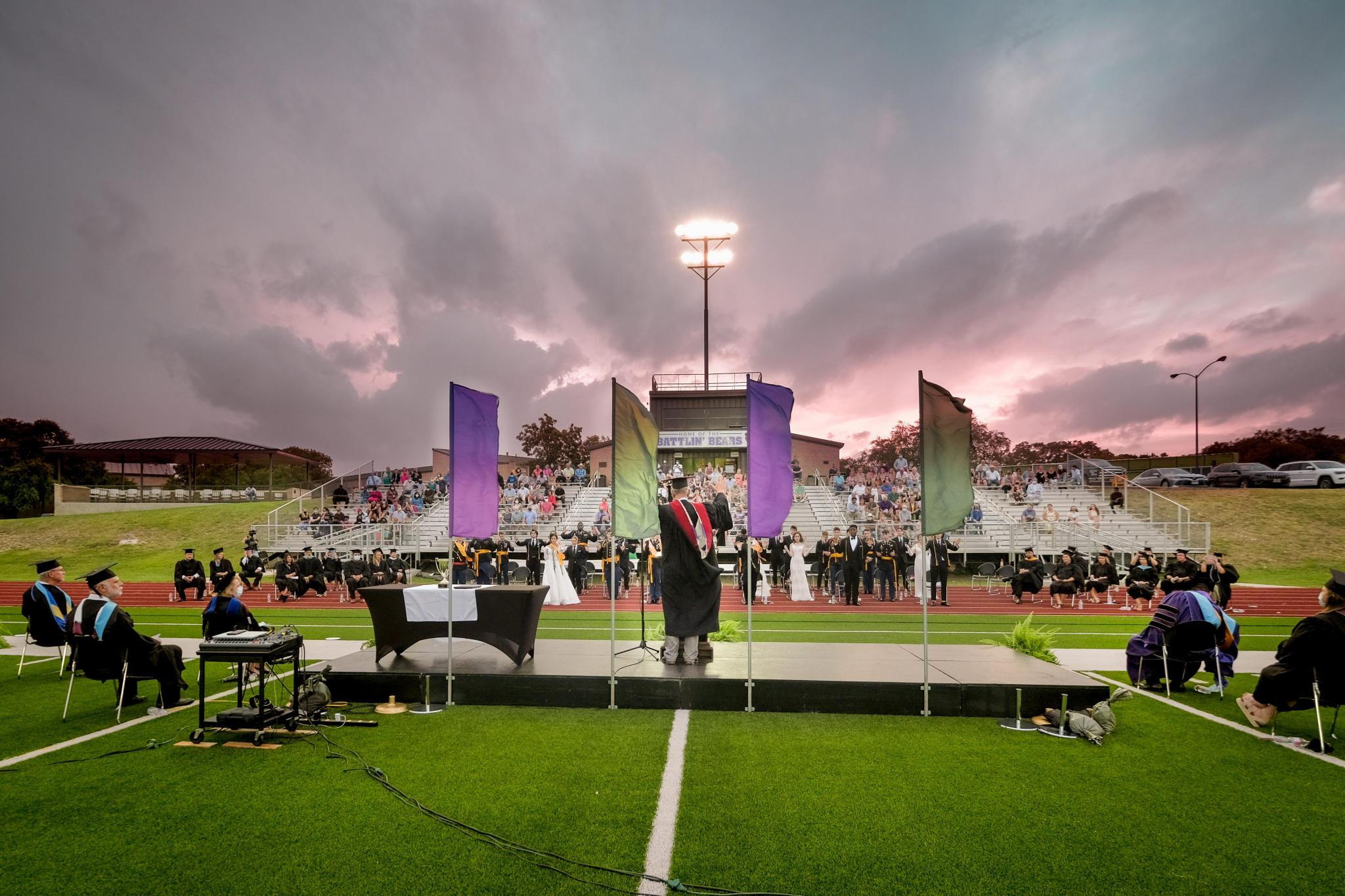 Col. Max Smith, a member of the Academy faculty, gives the Senior Class Blessing as the sun sets behind the stadium.