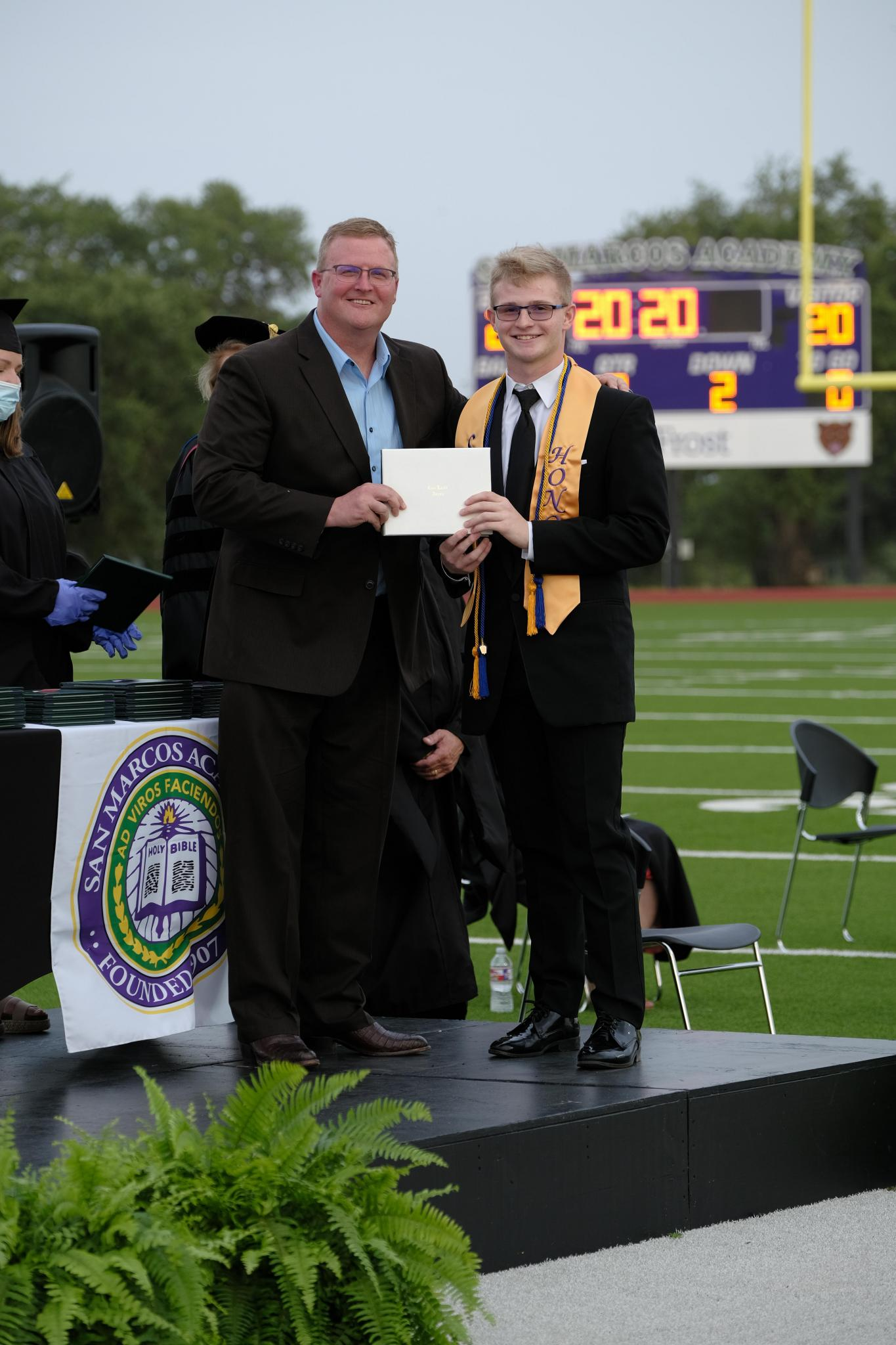 Austin Lee receives his cum laude diploma from his father, Dr. Lane Lee, a member of the Academy's Board of Trustees. Lee will attend Trinity University in San Antonio this fall to study engineering science and run track for the Tigers.
