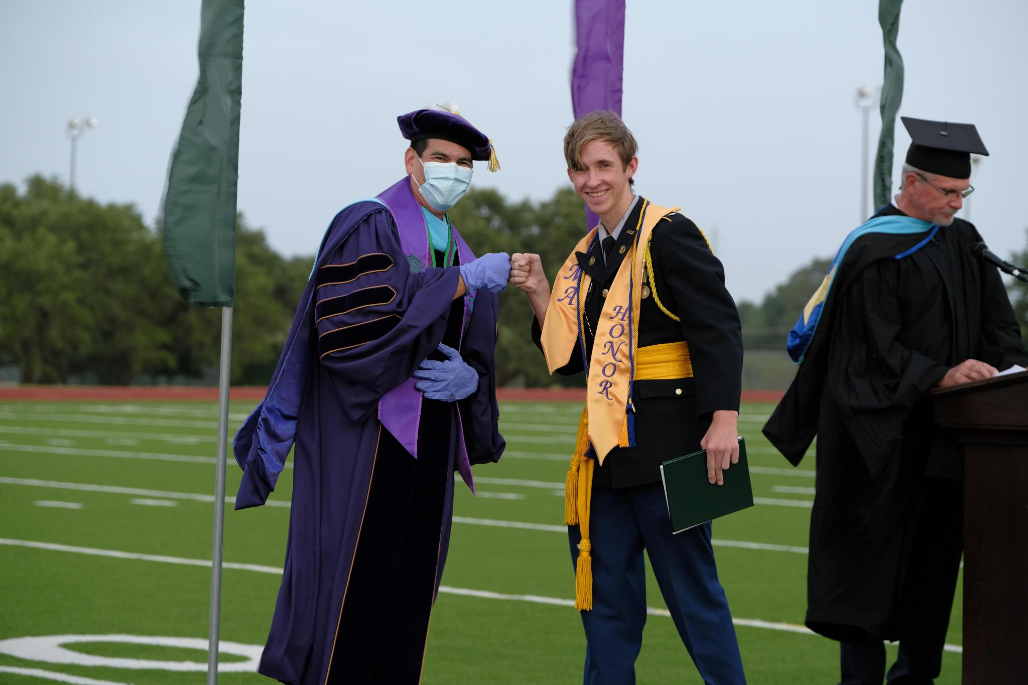 With a fist bump from President Brian Guenther, Caleb Strube of San Marcos celebrates receiving his cum laude diploma. Strube will enter Texas A&M at College Station as an Aggie Corps cadet this fall to major in political science.