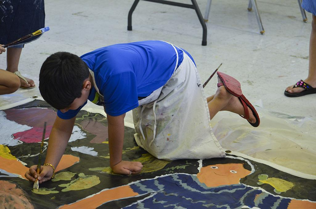 Arshaun Fallahi paints in some turtles after finishing up his merman for the mural.