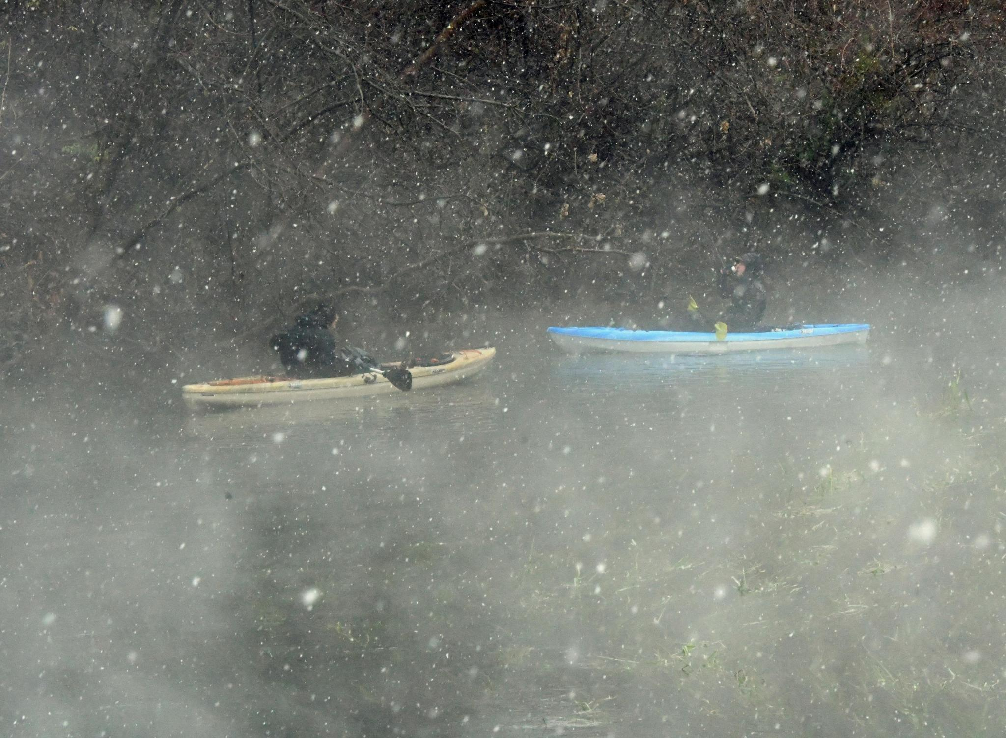 Above, kayakers paddle through the San Marcos River as snow begins to fall. For more photos of Sunday's snow day. Daily Record photo by Gerald Castillo